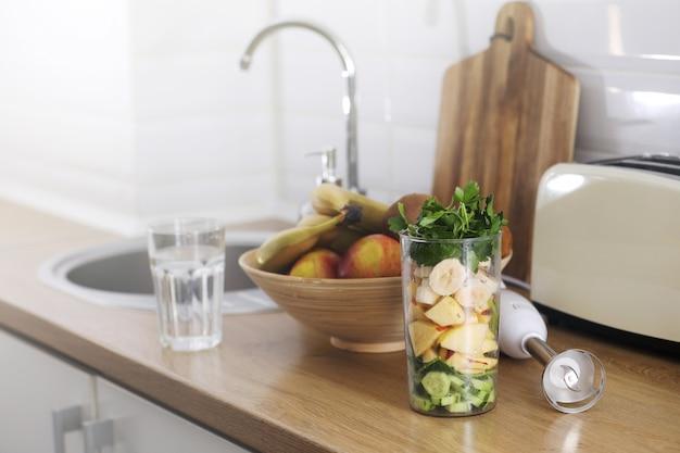 Frutta schiacciata per frullato. frutti tropicali e frullato differenti sulla tavola sulla cucina domestica, concetto sano di stile di vita di cibo. messa a fuoco selettiva.