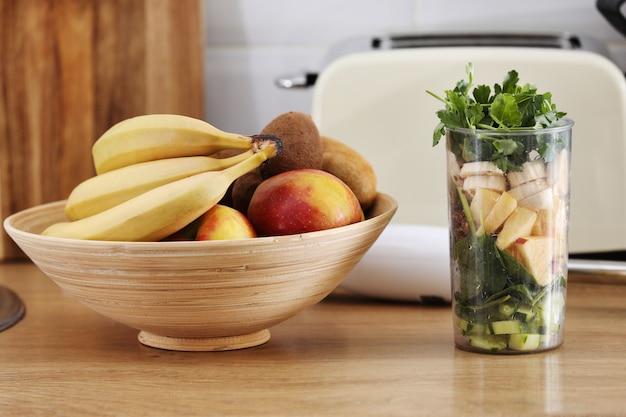 Frutta schiacciata per frullato. frutti tropicali e frullato differenti sulla tavola sulla parete domestica della cucina, concetto sano di stile di vita di cibo. messa a fuoco selettiva.