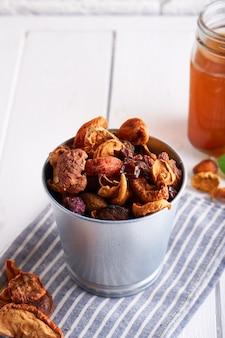 Frutta secca e composta fatta in casa di frutta secca in un barattolo su un tavolo luminoso.