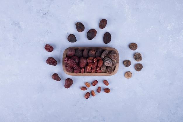 Frutta secca in un vassoio di legno e sul tavolo
