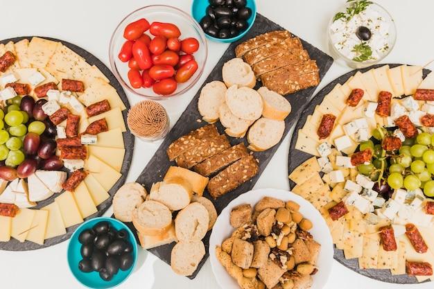 Frutta secca, olive, pomodori e piatto di formaggi con uva e salsicce affumicate