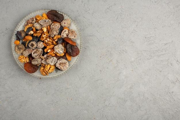Frutta secca una vista dall'alto di loro all'interno del piatto rotondo di vetro su una luce