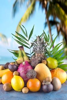 Frutta tropicale assortita sulla spiaggia arancia, ananas, lime, mango, dragon fruit, arancia, banan, rambutan e lichi