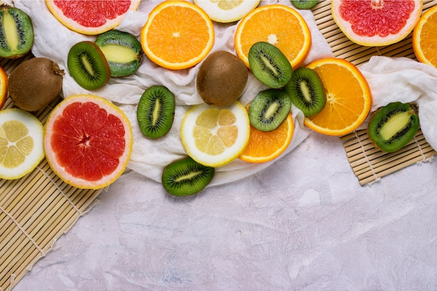 Frutta tropicale fresca, pompelmo, limone, arancia, kiwi su uno sfondo di pietra chiara.