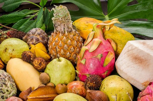 Frutta tropicale tailandese assortita su un fondo rustico di legno scuro.