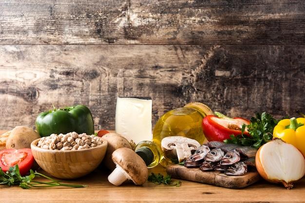 Frutta, verdura, grano, noci, olio d'oliva e pesce sul tavolo di legno