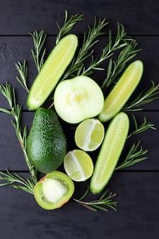Frutta, verdure e rosmarini verdi sui bordi neri con lo spazio della copia. avocado, lime, kiwi e mela verde su assi di legno. vista superiore di rami di rosmarino e cetrioli. cibo salutare