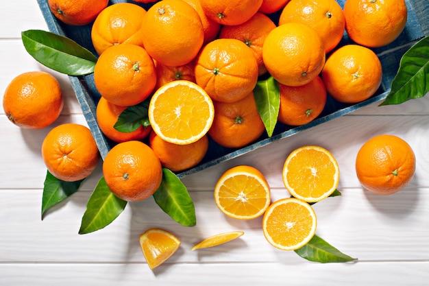 Frutti arancio freschi con le foglie sulla tavola di legno