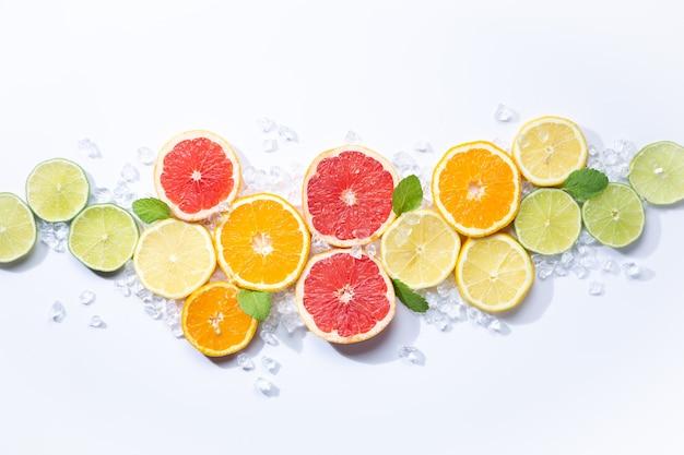 Frutti colorati sullo sfondo. fette di agrumi, arancia, limone, lime e pompelmo con ghiaccio e menta. sfondo bianco. vista dall'alto