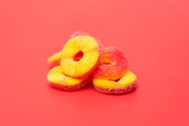 Frutti deliziosi della gelatina su fondo rosso