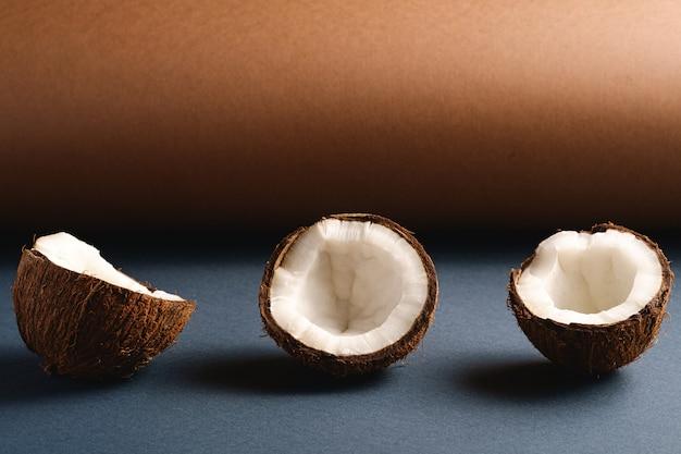 Frutti della noce di cocco sul fondo di carta piegato grigio marrone e blu