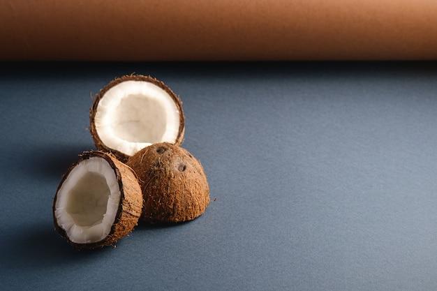 Frutti della noce di cocco sulla superficie della carta piegata grey marrone e blu, concetto tropicale dell'alimento astratto, spazio della copia di vista di angolo