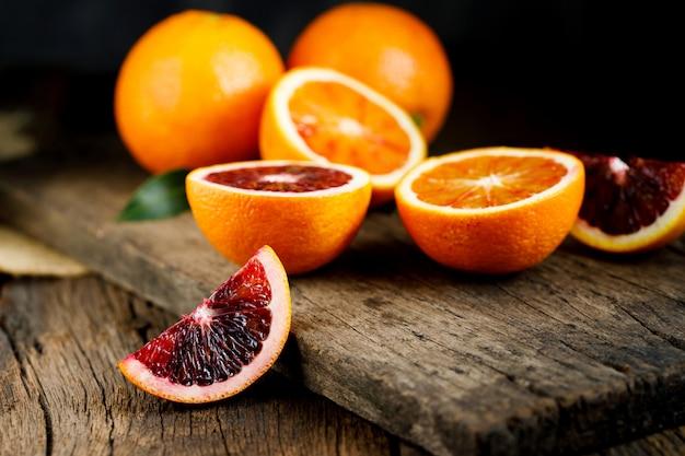 Frutti di arance rosse siciliane affettati sopra vecchio legno scuro.
