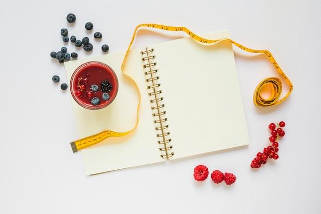 Frutti di bosco; bicchiere da frullatore; nastro di misurazione e quaderno a spirale su sfondo bianco