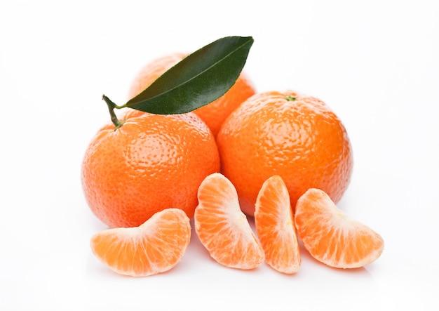 Frutti di mandarini organici freschi dei mandarini con le foglie su fondo bianco