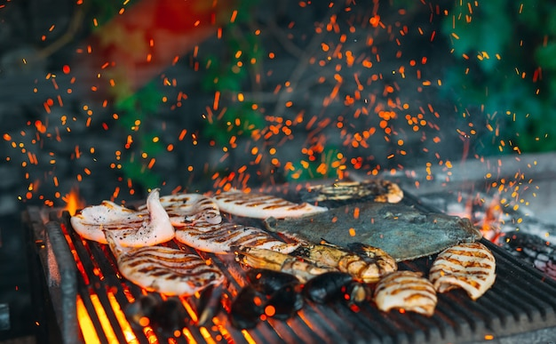 Frutti di mare alla griglia, cozze, gamberi, calamari e pesce sono cotti al fuoco.