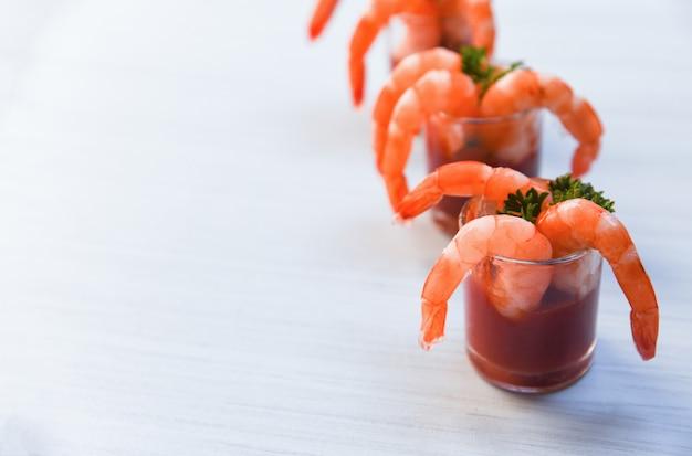Frutti di mare crostacei bolliti gamberetti gamberi ketchup e spezie nel tavolo da pranzo