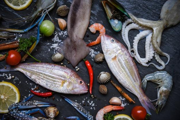 Frutti di mare crudi freschi con erbe e spezie limone su sfondo scuro