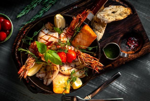 Frutti di mare grigliati in padella su una tavola di legno, gamberi, salmone, calamari con condimenti e salsa