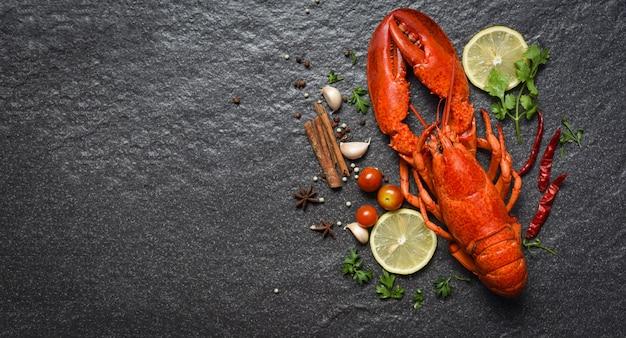 Frutti di mare rossi dell'aragosta con il copyspace di vista superiore delle spezie e delle erbe del limone