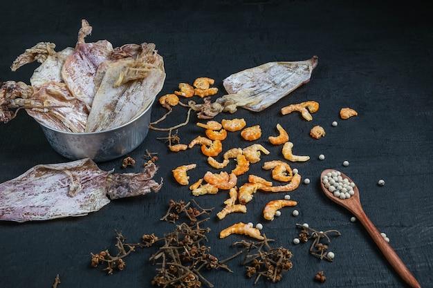 Frutti di mare secchi con calamari secchi e gamberetti essiccati su un tavolo di legno nero