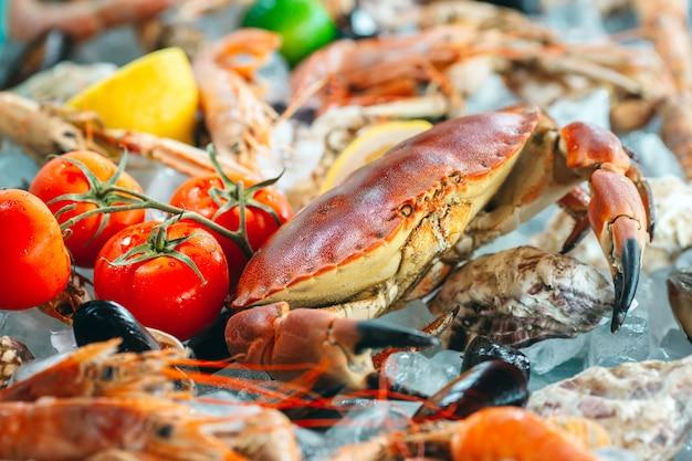 Frutti di mare sul ghiaccio. granchi, storioni, molluschi, gamberetti, rapana, dorado, su ghiaccio bianco.