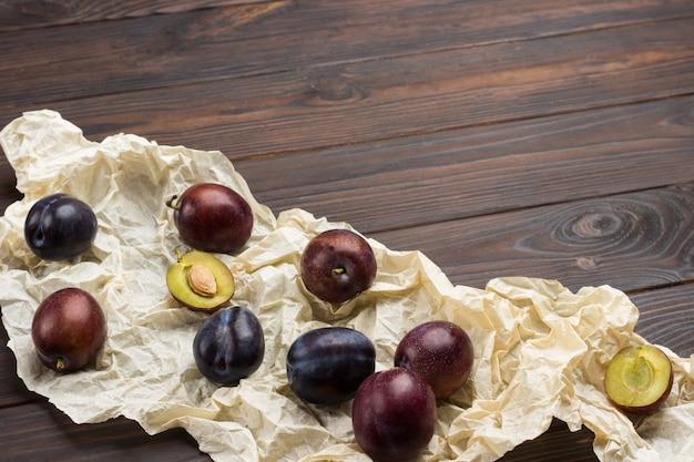Frutti di prugna su carta bianca. mezza prugna con nocciolo.