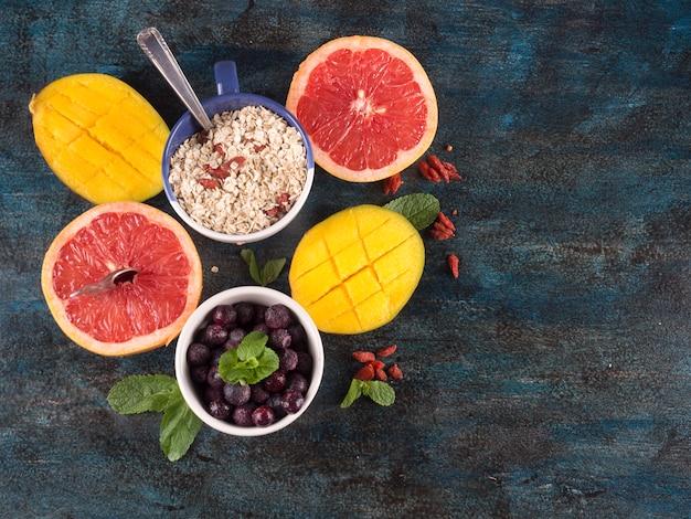 Frutti diversi con farina d'avena sul tavolo blu
