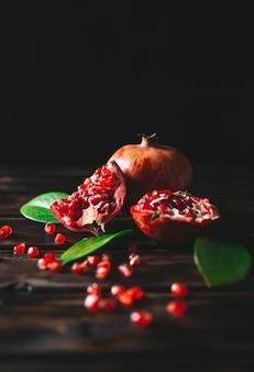 Frutti freschi del melograno interi e tagliati su una tavola di legno rustica