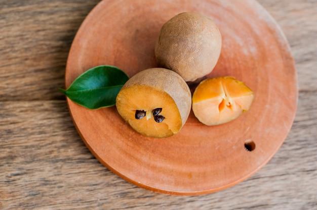 Frutti freschi della sapota su vecchio fondo di legno