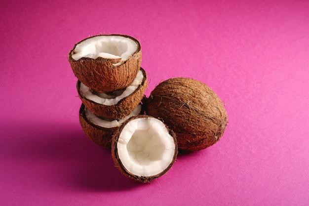 Frutti impilati della noce di cocco sul concetto tropicale dell'alimento dell'estratto della superficie della pianura porpora rosa