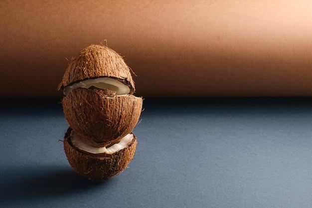 Frutti impilati della noce di cocco sulla superficie della carta piegata grigio marrone e blu