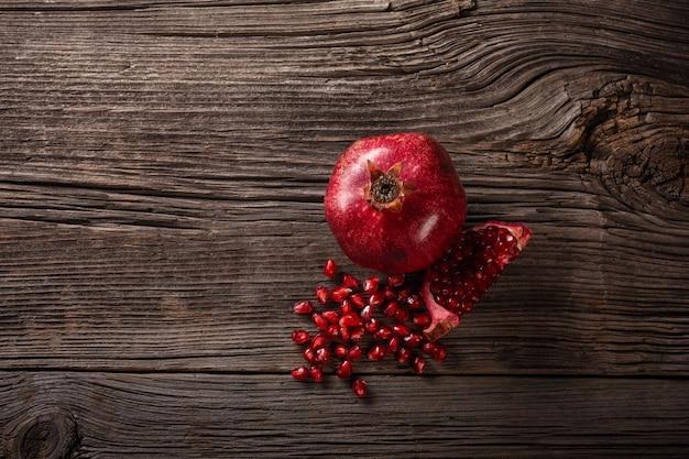 Frutti maturi del melograno sui precedenti di legno