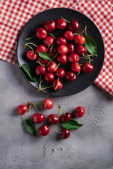 Frutti maturi freschi della ciliegia con le foglie verdi sulla banda nera con le bacche rosse della vitamina dell'asciugamano di piatto su fondo grigio di pietra,