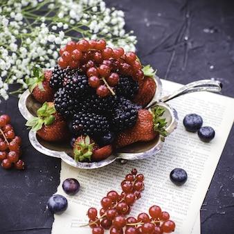 Frutti maturi multicolori freschi multicolori di vista alta vicina della parte anteriore come le more e le fragole rosse dentro di piastra metallica sul pavimento scuro