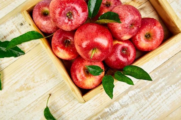 Frutti maturi rossi freschi delle mele nella scatola di legno