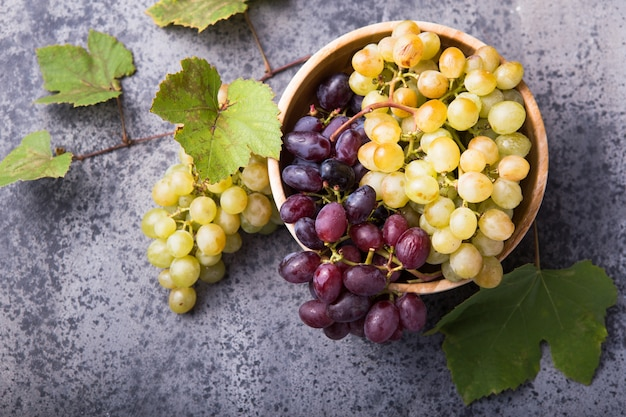 Frutti sani acini d'uva rossi e bianchi sulla superficie s della pietra