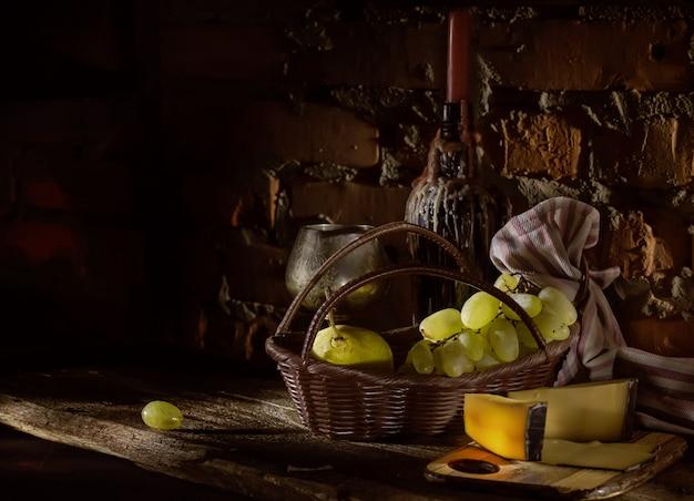 Frutti su un cestino e una bottiglia con una candela in una bottiglia di vino