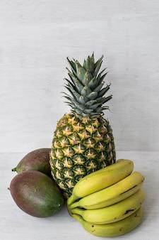 Frutti tropicali: ananas, mango e banane. sfondo bianco con spazio per copiare il testo