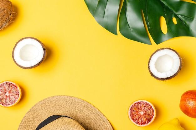 Frutti tropicali, arance rosse, cocco, cappello di paglia, foglia di palma