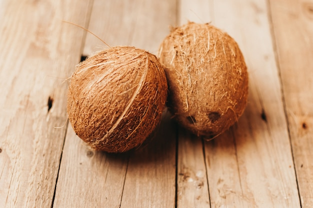 Frutti tropicali della noce di cocco su una tavola di legno nello stile rustico.