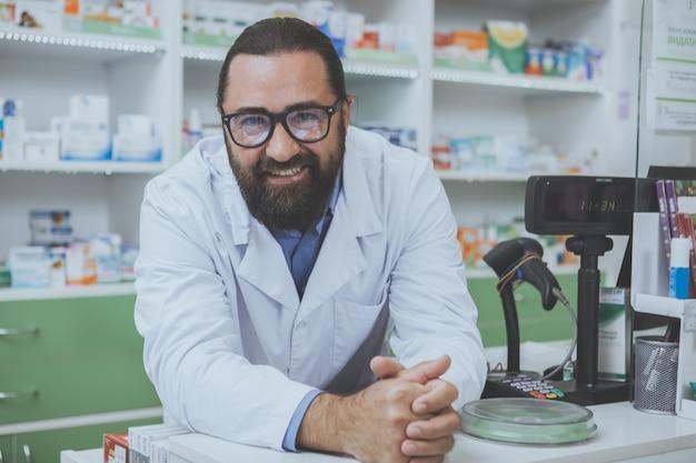Fruttivista barbuto maturo che lavora in farmacia