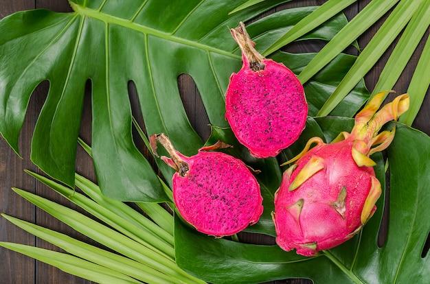 Frutto del drago sulle foglie di palma e mostro