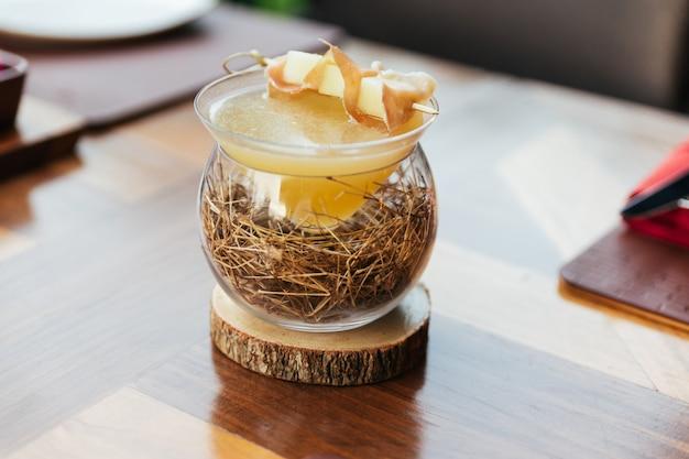 Frutto della passione cocktail giallo con spiedino di prosciutto di parma e ananas. servito in un bicchiere decorato con cannuccia.