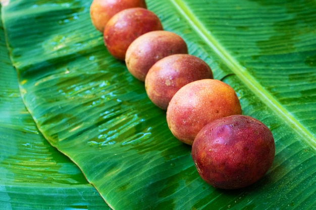 Frutto della passione maturo, su una foglia di banana bagnata. vitamine, frutta, cibi sani