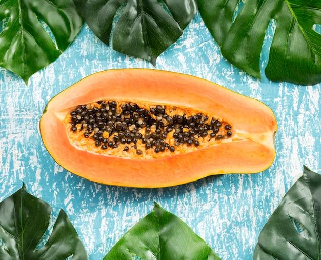 Frutto di papaia mezzo tagliato con foglie di monstera