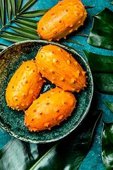 Frutto tropicale kiwano frutto della passione in una ciotola verde su turchese con foglie di palma tropicale. vista dall'alto. tropicale