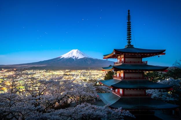 Fujiyoshida, giappone a chureito pagoda e mt. fuji in primavera con fiori di ciliegio in piena fioritura durante il crepuscolo. giappone