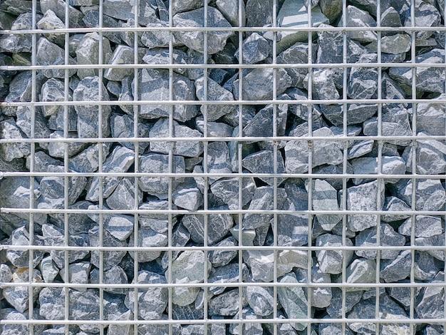 Full frame background of gravel stones parete con rete metallica