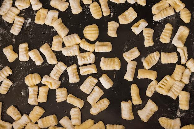 Full frame di gnocchi di pasta fatta in casa non cotti sul piano di lavoro della cucina